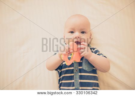 Cute Newborn Baby Takes A Wooden Toy In His Mouth. Teething And Health Concept