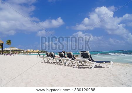 Sandy Beach On The Ocean The Gulf Of Mexico Cancun, White Sand, Girls Relax On Sunbeds, Different Ty