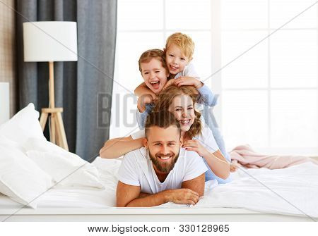 Happy Family Mother, Father And Children Laughing, Playing And Smiling In Bed In Bedroom At Home