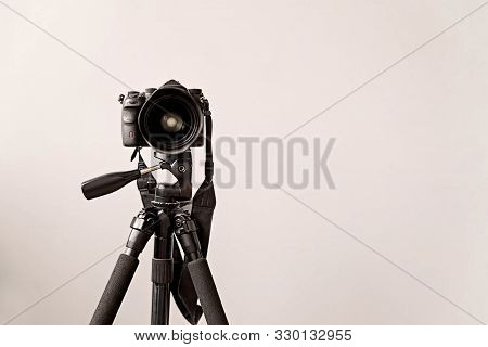Photography Concept. Professional Camera On The Black Tripod Isolated On Gray Background With Copy S