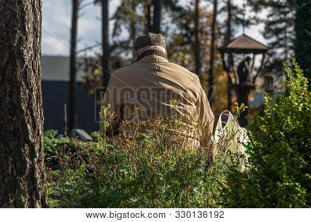 An Old Gray Man In A Light Coat And Hat Mourns At His Passing Grave In A Cemetery In The Fall On A S