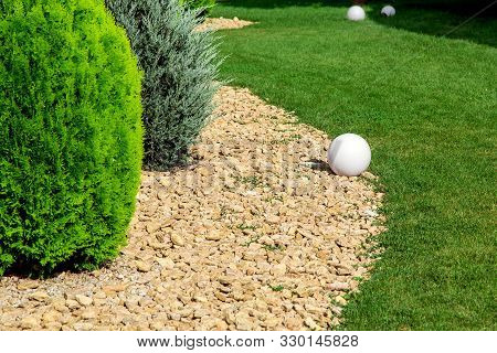 The Landscape Design Is Scattered With Stones In Which Evergreen Thuja Bushes Grow And Along The Edg