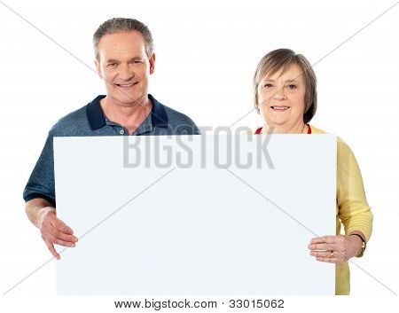 Smiling Aged Couple Holding Blank White Poster