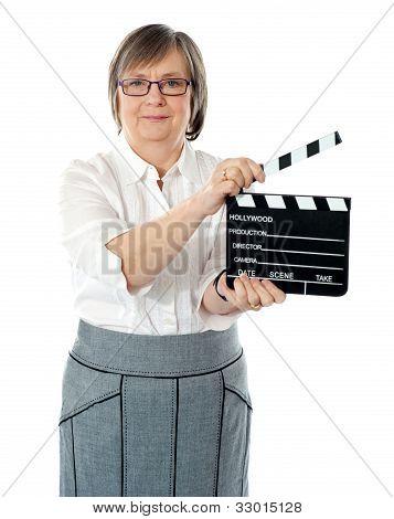 Attractive Senior Woman Using Clapperboard