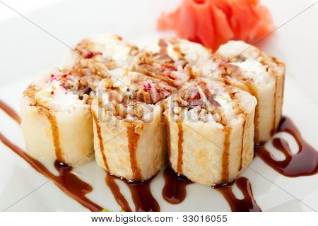 Maki Sushi - Roll made of Smoked Eel, Cream Cheese and Tobiko inside. Tamago (japanese omelet) ouside. Garnished with Sauce