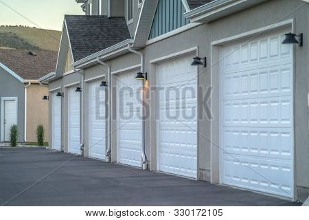 Focus On The White Garage Doors Of Townhousesflanked By Outdoor Wall Lamps