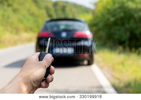 Picture Of The Man Holding  Car Key, Opening His Brand New Black Car