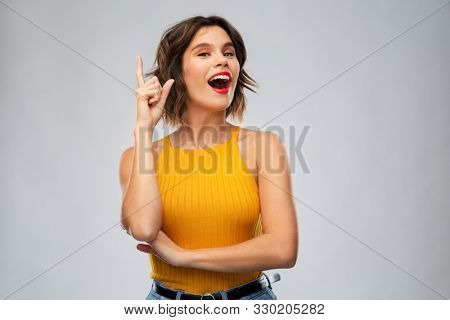 gesture, idea and people concept - happy smiling young woman in mustard yellow top pointing finger up over grey background