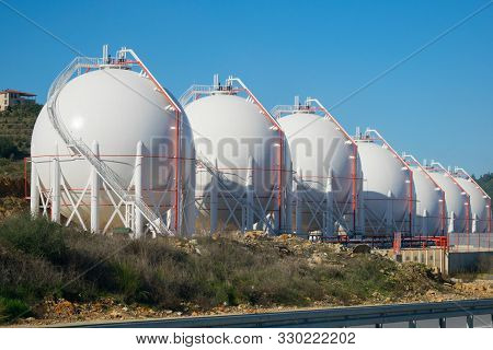 Lng Storage Tanks. Seven Gas Containers By The Road.