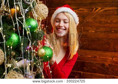 Cute Girl Is Decorating The Christmas Tree Indoors. Christmas Decorations. Fashion Portrait Of Model