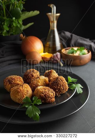 Homemade Croquettes On Dark Wooden Background, Ingredients For Its Elaboration In The Background