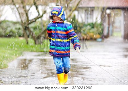 Little Kid Boy Wearing Yellow Rain Boots And Walking During Sleet, Rain And Snow On Cold Day. Child