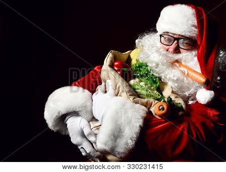 Jolly Santa Claus Is Holding A Big Sack Full Of Fruits And Vegetables. Enjoy A Healthy Christmas Din