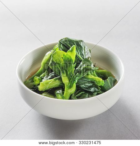 Boiled Spinach In Season With Soy Sauce In A White Ceramic Dish