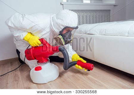 Pest Control Worker Lying On Floor And Spraying Pesticides In Bedroom