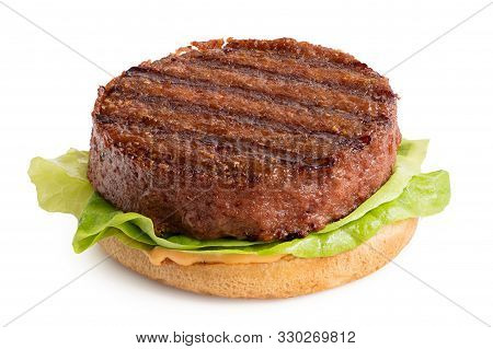 Freshly Grilled Plant Based Burger Patty On Bun With Lettuce And Sauce Isolated On White.