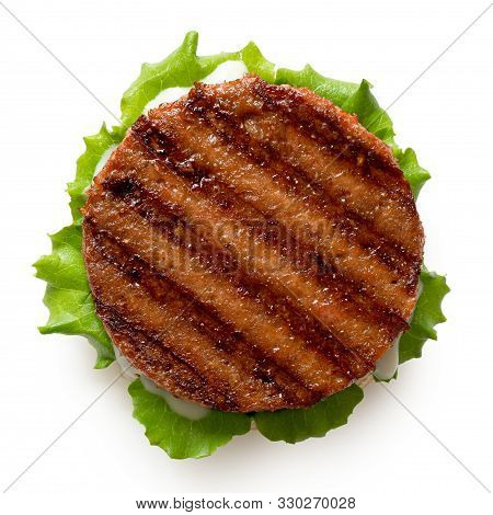 Freshly Grilled Plant Based Burger Patty On Bun With Lettuce And Sauce Isolated On White. Top View.
