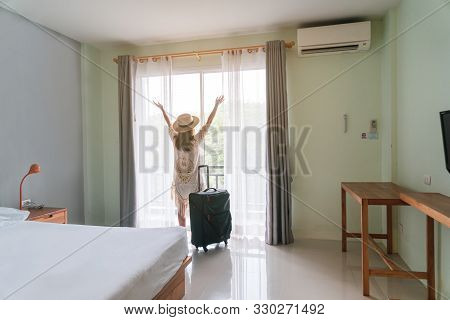 Young Woman Traveler With Luggage Looking At View In Hotel Room On Summer Vacation