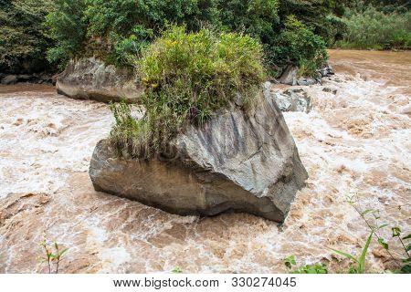 Big rock on Urubamba river near Machu Picchu (Peru) following the Andes Mountains in Peru between Cusco and Machu Picchu. Peru. South America.