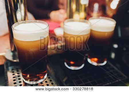 Close Up Of A Male Bartender Dispensing Draught Beer In A Pub Holding A Large Glass Tankard Under A