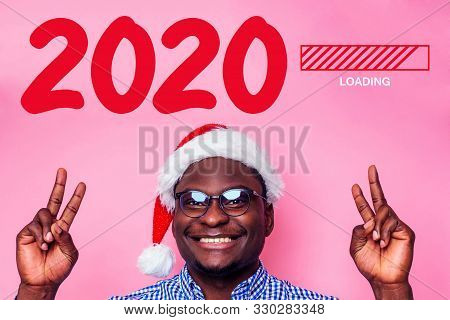 Loading New Year 2020 With African American Man With Great Smile In Santa Hat On Pink Background Stu