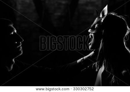 A Man In A Shirt Holds A Submissive Lover By The Neck. A Woman In A Leather Cat Mask Bites A Leather