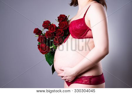 Pregnant Woman With Red Roses Bouquet On Gray Background