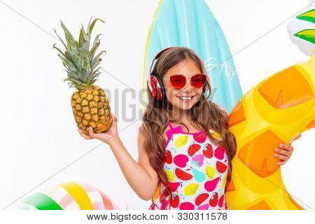 Closeup Smiling Girl On A White Background, The Child Holds A Pineapple In His Hands Surrounded By S