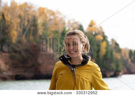 Cute Adult Female Wearing A Tyellow Rain Jacket Poses On A Boat Near The Apostle Islands National La