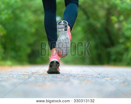 Running Woman In The Forest. Close-up Of Sneakers. Helathy Lifestyle Concept.