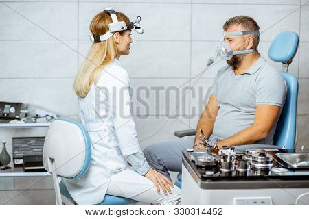 Adult Man During A Medical Breathing Treatment With Respiratory Mask Against Snoring Sitting With Do