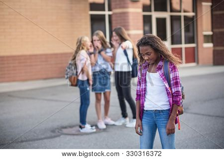 One student being bullied and talked behind back while other students gossiping. Social and school bully concept.