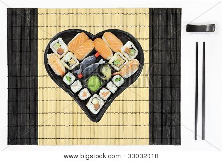 Sushi and sashimi in heart shape on tablemat