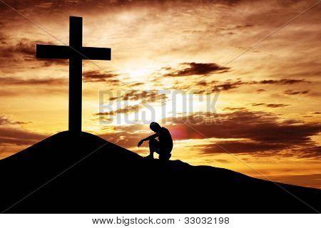 Mann, sitzend verzweifelt unter dem Kreuz