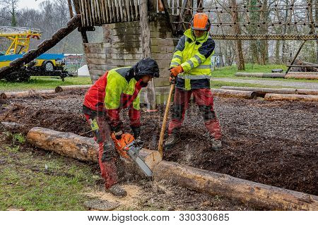 Young Loggers Working On A Playground, Cutting Tree Trunk With Chain Saws In Rainy Day.