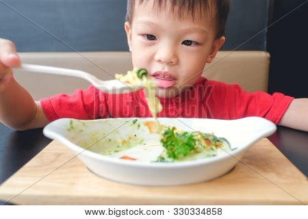 Cute Asian 3 - 4 Years Old Toddler Boy Child Eating Baked Spinach With Cheese With Spoon For Lunch A