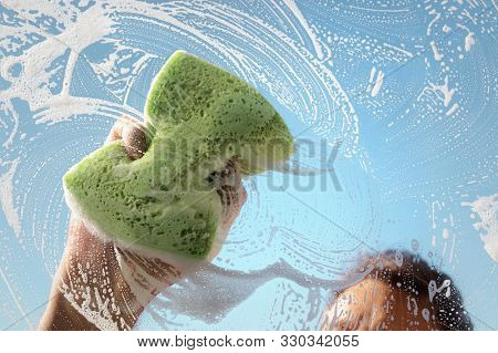 Window cleaner using a sponge to wash a window with clear blue sky