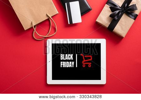 Black Friday Sale Concept. Tablet With Black Friday Mockup On Screen And Shopping Accessories Over R