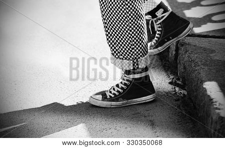 A Black-and-white Image Of The Feet Of A Man Descending, Dressed In Fashionable Plaid Pants And Snea