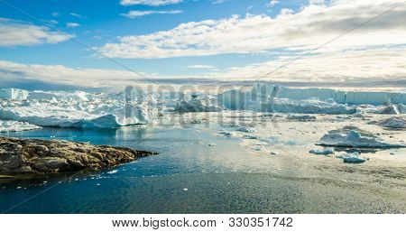 Iceberg and ice from glacier in arctic nature landscape on Greenland. Aerial image drone image of icebergs in Ilulissat icefjord. Affected by climate change and global warming.