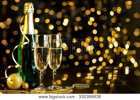 Two Glasses And Green Bottle With Champagne, Gold Decor, Balls, Serpentine Are On Table. Festive Dec