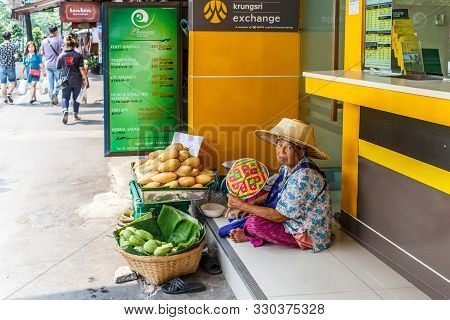 Bangkok, Thailand - 23rd March 2018: Old Woman Sat In The Shelter Of An Exchange Booth On Sukhumvit