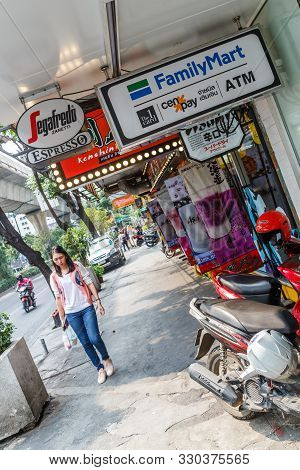 Bangkok, Thailand - 23rd March 2018: A Woman Walks Past Signage On Sukhumvit Road. The Road Is In Th
