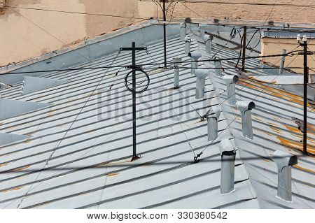 Cropped Photo Of Multiple Ventilation Pipes From Stainless Steel And Antenna With Wires On The Rooft