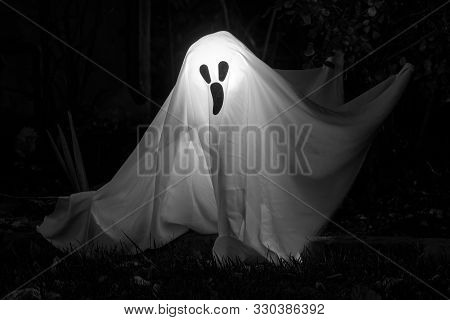 White Ghost on Dark Background. Halloween Décor Outside Residential Building. poster