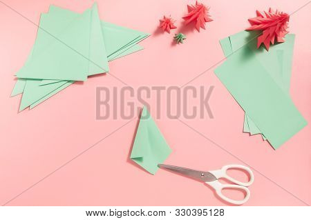 A Process Of Making 3d Fir Tree From Green Paper On Pink Background. Step By Step Instruction, Step