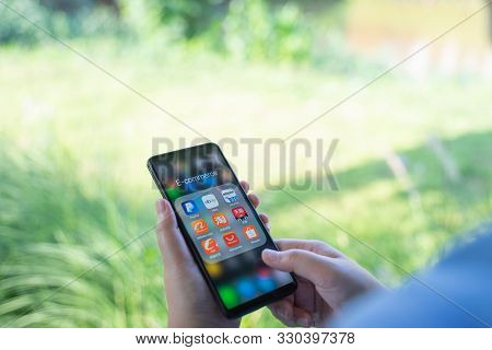 Chiang Mai, Thailand - Oct.18,2019: Woman Holding Xiaomi Mi Mix 3 With Icons Of E-commerce And Onlin