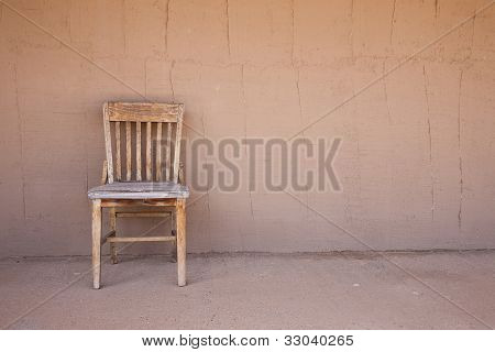 Old Western Chair Against An Adobe Wall