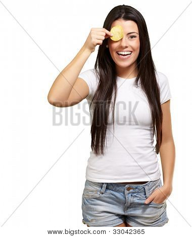 portrait of a young woman holding a potato chip in front of her eye over a white background