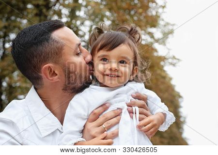 Father Kissing Her Cute Little Baby Girl In The Park